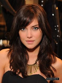 Jessica Stroup with side swept bangs and wavy medium to long hair.