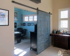 This blue barn door separates an office space and entertainment room.