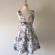 Palm Skater Dress BNWT Beautiful skater dress with light coral and blue palm graphic. Banded at the waist. Plunging neck line. Brand new and never worn, cut the tags off because I was planning on wearing this to a wedding but changed my mind!  Dainty Hooligan Dresses Mini