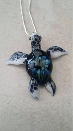 The spotted flipper sea turtle has white flippers with black and some times brown speckels or spots on its flippers. The Spotted flipper Sea Turtle is the smallest sea turtle pendant that we offer. This glass sea turtle pendant necklace is about 1-1/4 to 1-3/4 inches longfrom head to tail. Size and coloring can vary slightly. However I can assure you that each one is very vibrant and a work of art! This is a beautiful pendant or could be used as beach jewelry. This one turned out ve...