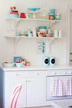 küche im shabby chic stil, weiße schränke, hölzerne regale mit tassen und tellern