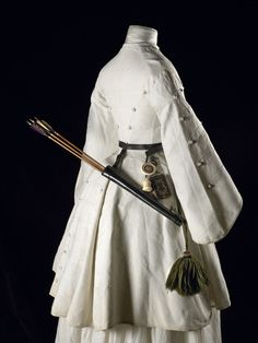 A three quarter length white cotton Marcella archery jacket with pagoda sleeves, trimmed in military style with braid and covered conical buttons. Worn by Mrs. Fanny Giveen, the wife of Captain Xavier Giveen, in 1855.