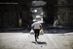 """<b>Marco Longari</b></br><br> """"It was shortly after I traveled to Aleppo that I went trying to photograph at a checkpoint in the old city. By mid-morning, I saw this man. He approached an FSA checkpoint. Gunfire, although sporadic, was directed at everyone trying to cross the street. <br><br> He arrived, bags of groceries in hand, dignified. A civil servant, a teacher — an ordinary Syrian taking care of his family's needs. When I saw him there hesitating, I thought of what would have been…"""