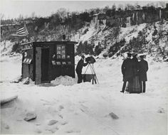 ca. 1880, [tintype photographer in front of his booth photographing a group in the snow], Robert L. Bracklow