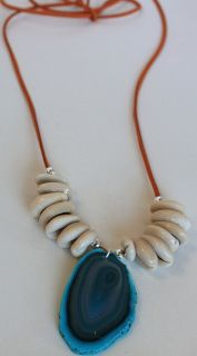 item #N024-CT The slice of heaven necklace- is made by the combination of hand selected deep teal agate slice set with beautiful cowrie shells and silver beads are all strung on chestnut faux suede cord. Can also be worn as a bracelet (as shown in picture).
