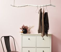 Paint a sturdy branch of wood, hang it from the ceiling, and you've got yourself a clothes hanger