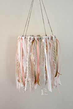 Mobile in creamy beige, gold and hints of coral.  This stunning mobile is packed full of lace, fibers and ribbon.  Meters of materials were used when creating this piece!  Pictured mobile measures 8 across hoop Each piece of lace and ribbon hangs approx 13 long. Measures approx 27 in length including the twine hanger.  So soft, pretty, and dreamy! Perfect for a little girls nursery.  It will add the perfect finishing touch to any occasion or special space in your home!   Lace pattern and…