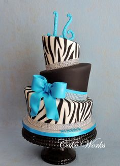 Sweet 16 Zebra and Bling - Topsy turvy sweet 16 birthday cake. The bling is faux rhinestone wrap, bow and 16 are gumpaste. The flavor was white almond cake with raspberry filling.