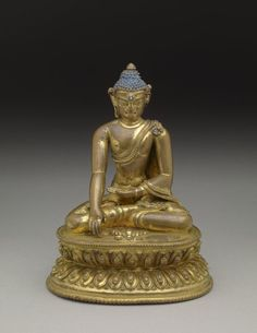 Figure. Made of gilded bronze. Sitting in vajrasana on double lotus base. Right hand in bhumisparsamudra, left in dhyanamudra. Diamond set in vajra, turquoise in forehead. British Museum