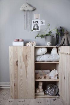 einfacher Holzschrank im Kinderzimmer im skandinavischen Look schön eingerichtet und dekoriert