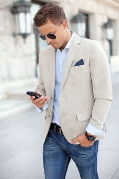 Dress in a beige blazer and blue jeans for a sleek elegant look. Shop this look for $247: http://lookastic.com/men/looks/pocket-square-and-longsleeve-shirt-and-blazer-and-belt-and-jeans-and-sunglasses/3932 — Navy Pocket Square — Light Blue Longsleeve Shirt — Beige Blazer — Burgundy Leather Belt — Blue Jeans — Black Sunglasses