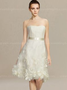 Short beach wedding dress features handmade petals and satin ribbon at waist. Strapless bodice is subtly pleated and makes this entire look dainty and demure. Knee length skirt looks sweet and graceful.