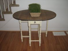 Antique gate leg table that was given to me, it goes back to the 1800s and is in perfect condition.  I had it in my basement collecting dust for a couple of years.  It had a very dark stain on it almost black, I sanded the top and waxed it, I also painted the legs cream and distressed to show some of the original stain.  Then I changed the knob to a crystal for a little bling