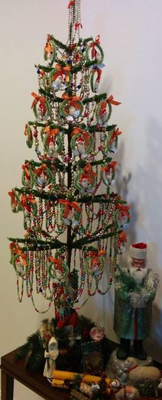 "Antique Decorated Tree with a collection of ""Bottle Brush Wreaths"" (with Santa face and red bows) and lots of ""antique glass bead chains"". Terrific looking tree,with antique Belsnickle Santa Candy Container below it, with other antiques."