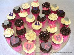21st Birthday Cupcake Selection. A selection of swirly buttercream cup cakes decorated with sugar icons and degree balls, purple glitter 21s and the name letters mounted on sugar hearts
