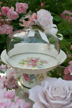 A tea cup base, a pretty plate on top and an old cheese board dome