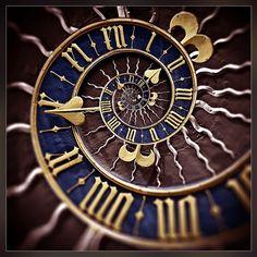 unusual clock face - like a spiral,a sun, using roman numerals.