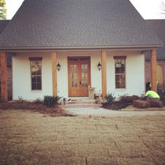 Acadian farmhouse front porch. Sherwin Williams Swiss Coffee on front porch.