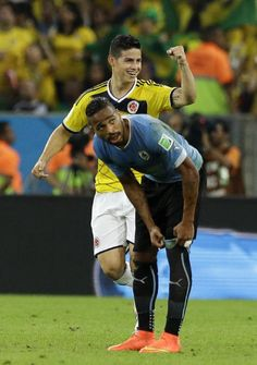 Colombia's James Rodriguez, rear, celebrates as he walks past Uruguay's Alvaro Pereira after scoring his side's first goal during the World Cup round of 16 soccer match between Colombia and Uruguay at the Maracana Stadium in Rio de Janeiro, Brazil, Saturday, June 28, 2014