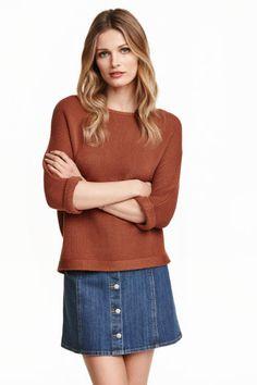 Gebreide trui: Een averechts gebreide trui van katoenmix met driekwart mouwen met een vastgestikte omslag onderaan.