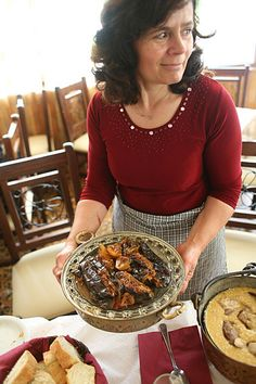 The owner of Gormos taverna in the village of Parakalamos, in Epirus, serving a plate of roasted eggplant.