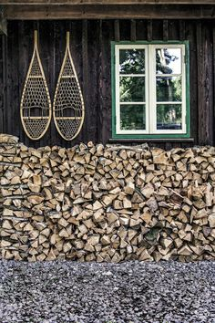 firewood stack under eave & snowshoes