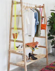Une dressing ouvert fait de planches en bois entre deux échelles