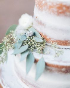 This delicious cake doubled as the perfect setting for photos of the wedding rings!  Photography: @photographybymicahlawilson /  Flowers: @leanne.graves / Food: Prepared and served by family & friends / Cake: Made by a family friend / Macrame backdrop: @wildbohemedesigns / Dress: @annacampbellbridal / Hair & Makeup: Hope Fontenot  #wedding #smallwedding #intimatewedding #beautiful #bride #groom #weddingdress #love #couple #yum #cake #weddingcake #weddingphotography #engagementring