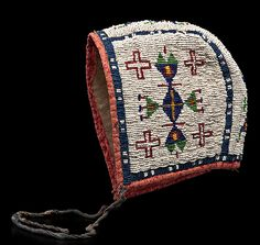 Sioux Baby Bonnet  thread and sinew-sewn and beaded using colors of pea green, red white-heart, dark blue, greasy yellow; lined with linen and edged with red patterned cotton, length 7 in. x width 5.5 in.  late 19th century; Cowan Auction