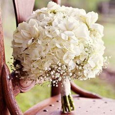 bridal bouquet combined white hydrangeas with baby's breath .  LOVE!