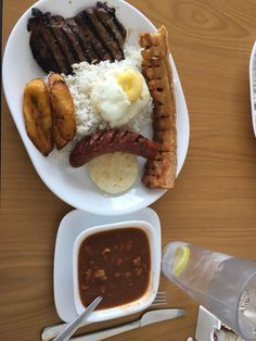 [I ate] this columbian feast yesterday: pork crackling grilled steak red sausage egg plantain beans and rice.