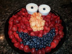 Fruit Face Elmo.. Strawberries Washed and cut in half long ways and blueberries for the eyes and mouth.. Clementines for the Nose..  White dishes for the eyes filled with vanilla Yogurt (i used the greek vanilla here)   Another tasty treat that was gone quickly by the guests :) Displayed on a 16 inch Plastic Plate in Black.