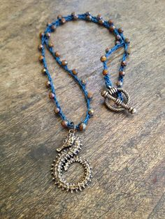 The colors of this necklace are stunning! Gorgeous Picasso Czech beads are crocheted onto teal blue nylon cord featuring a stunning artisan