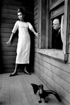 Alfred Hitchcock with model Ina Balke at the Psycho House, photographed by Jeanloup Sieff for Harper's Bazaar, 1962