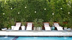 Sleek lounge chairs topped with tangerine-trimmed pillows are ready and waiting poolside. Hanging Lanterns, Hanging Lights, Outdoor Living Areas, Outdoor Spaces, Orange Pillows, Living Room White, Los Angeles Homes, Swinging Chair, Cushion Fabric