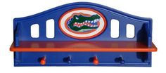 "Fan Creations Florida Gators Shelf With Pegs by Fan Creations. $49.99. Wood shelf. Decorated with a carved team logo. 4 pegs for hanging jackets and hats. Officially licensed. Dimensions: W 21"" x H 10.75"" x D 5"". Spruce up your little fan's room with this NCAA® shelf from Fan Creations®. It boasts a durable wood construction, includes 4 pegs that are perfect for hanging jackets and hats, and is decorated with a carved team logo."