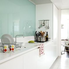 Narrow white kitchen  This pristine white scheme is offset by the green-tinged glass splashback. Glossy surfaces allow light to bounce around this kitchen, making it appear larger.