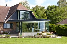A dining room extension incorporating curved structural glazing, a zinc roof and a frameless bay window.