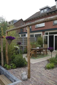 Achtertuin met overdekte zitkuil, wintergroene beplanting en pergola van kastanjehout www.vrielinktuinlink.nl