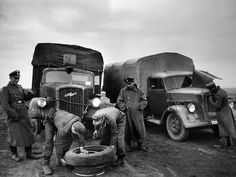 Soldiers from the 5 SS-Panzer-Division Repairing a Pumptured wheel on a Opel Blitz 3.6-36S.