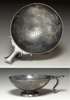 A BYZANTINE SILVER CUP   Circa 5th-7th Century A.D.   The shallow vessel on a short cylindrical stem and wide foot, the single handle with flat thumbrest and down-curving finger loop, the tondo of the vessel engraved with a chi-rho within two concentric circles, the underside of the foot engraved with a star  4½ in. (11.4 cm) long; 1 3/8 in. (3.5 cm) high