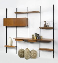 The 'Sistema E22' modular shelving system designed by Osvaldo Borsani in the 1950's, with a few stoneware and ceramic pieces including works by Lea Halpern and Claude Conover. Photo: Sothebys #mcmdaily #oswaldoborsani #leahalpern #claudeconover #usa #thenetherlands #italy mcmdaily.com