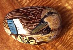 This duck has been hand painted onto a smooth stone and glazed for a glossy protective finish.