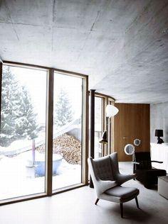 Zimowe wnętrze z widokiem na patio w ziemiance mieszkalnej Ville Vals. Proste, oszczędne, zachowawczy -idealne wnętrze ziemianki. Surowy beton architektoniczny ocieplony jedynie drewnem czyli naturalne materiały w wykończeniu wnętrza Twojego salonu.