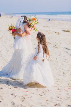 Flower girl watches as bride and maid of honor hug at beach wedding in Wrightsville Beach, NC