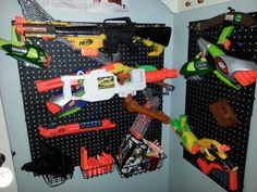My 10-yr-old's Nerf Gun Storage corner. Pegboard and pegs from Home Depot. 4 and 6 inch pegs can hold 2 or 3 stacked shotguns or huge guns. 2 inch pegs can hold smaller guns. Also good for swords and other long, pokey things that children may own. 3 pegboard baskets at the bottom hold dart containers and shells. About $80 and completely worth it!