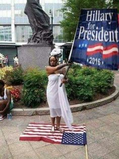 Standing on the American Flag, holding up a Killery for President. Now doesn't that just say it all.