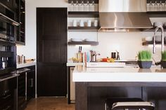 Open shelving with stainless steel hood between. Industrial faucet at the island. Caesarstone white countertops.