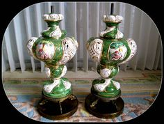"""This antique pair of hand painted Capo di Monte table lamps are with 3 detailed separate scenes on each.  Depictions of Adam & Eve finding the forbidden fruit, deciding to eat it and hiding after the act.  Scenes are separated by 3 pierced porcelain concave ovals.  The  color is a brilliant green with vibrant other colors. The accents are done in 22 ct. gold. Early 20th century. Brass pedestal base comes to 4 dolphins resting on a 7"""" diameter pierced brass circular platform."""