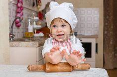 Kleines Mädchen in der Schürze und Mütze des Kochs mit Nudelholz sitzt am Esstisch in der Küche im Haus. Helfer der Mutter. 2 Jahre alt.